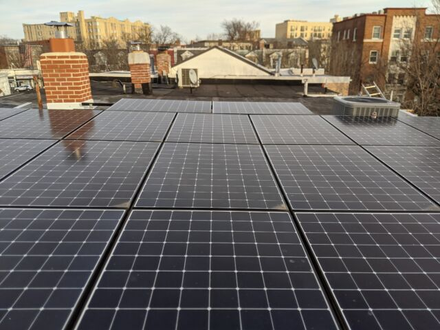 My roof has 8.5 kW of solar panels on it. In the background you can see our rebuilt chimney and the condensing unit for the heat pump.