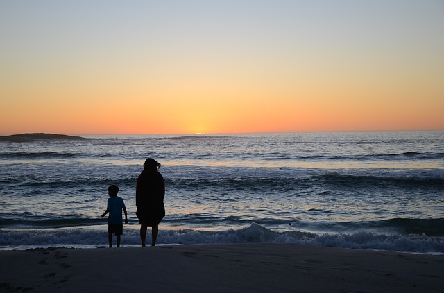 family walking on a beach at sunset