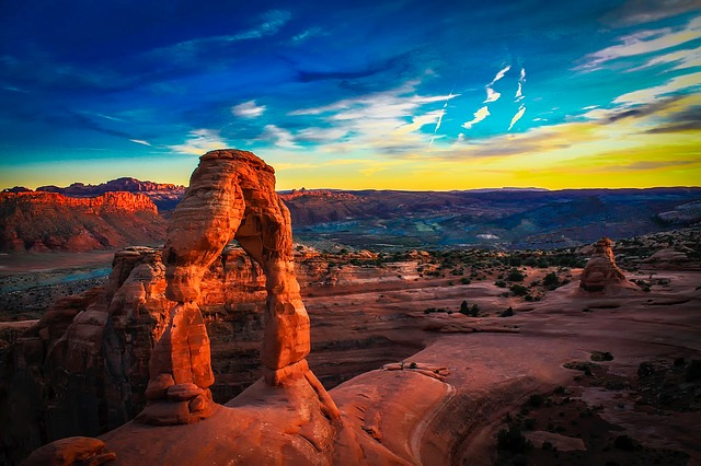 a red arch at Arches National Park with blue skies beyond
