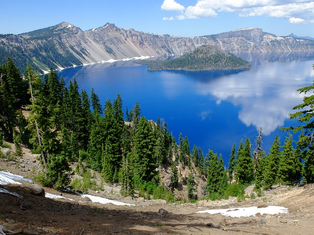 a sunny day at Crater Lake National Park, with patches of snow on the ground