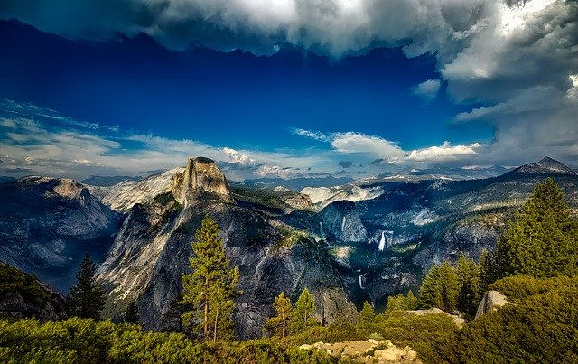 panoramic view of Yosemite, including Half Dome rising in the distance