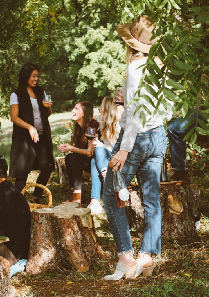 women outdoors laughing and drinking wine