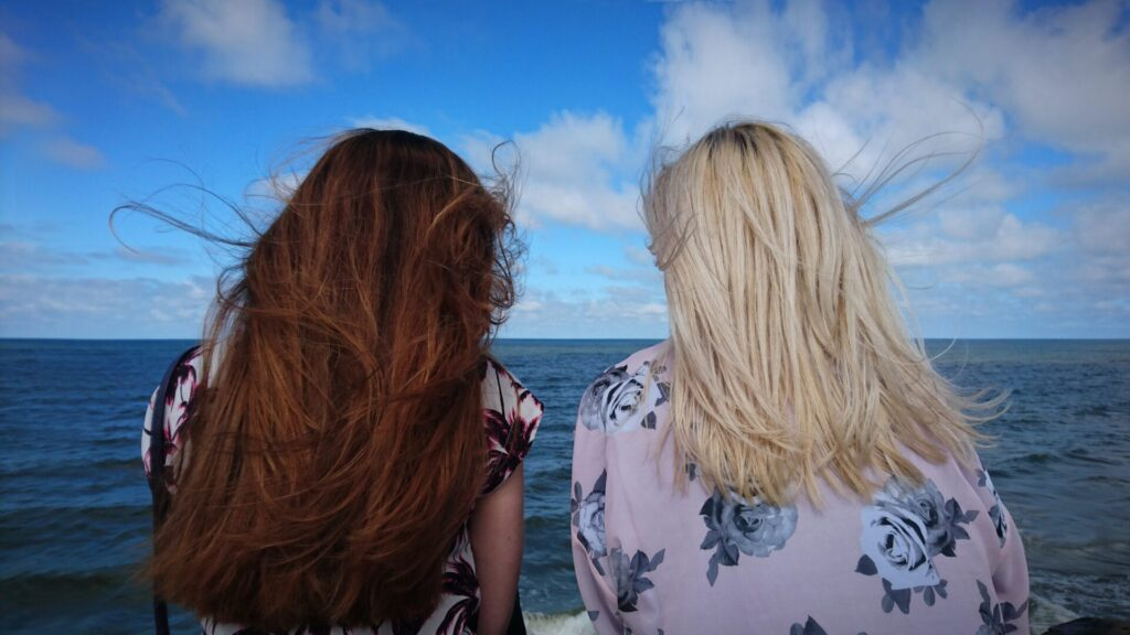 two women looking over a sunny beach