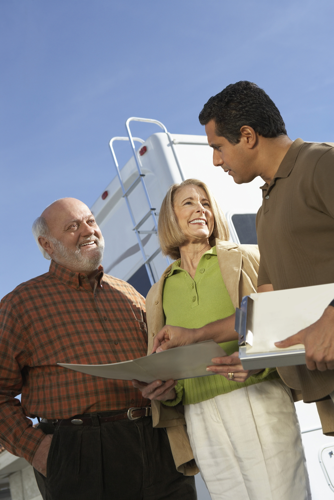 three people standing in front of an rv with paperwork