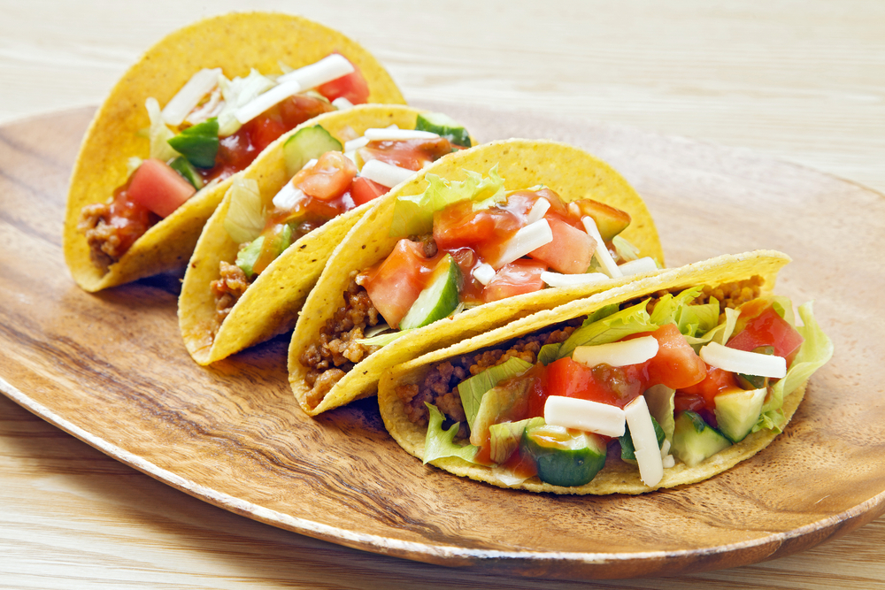 Lineup of four ground turkey tacos in hard corn shells garnished with tomatoes, lettuce, and avocado