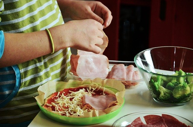 close up shot of kids hands as they prep ingredients for pizza