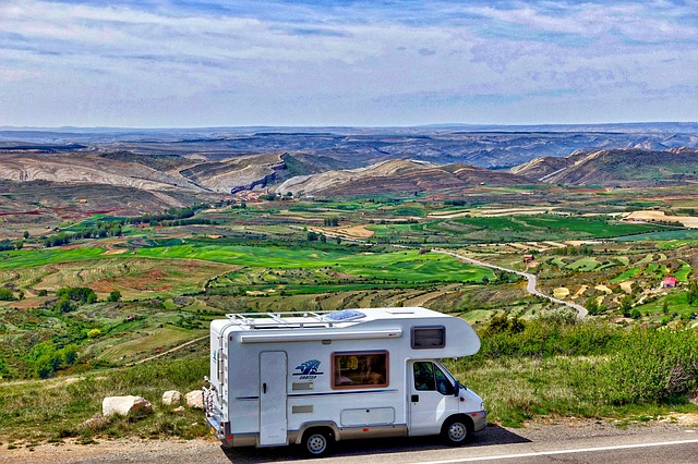 an RV driving past a green meadow with hills beyond