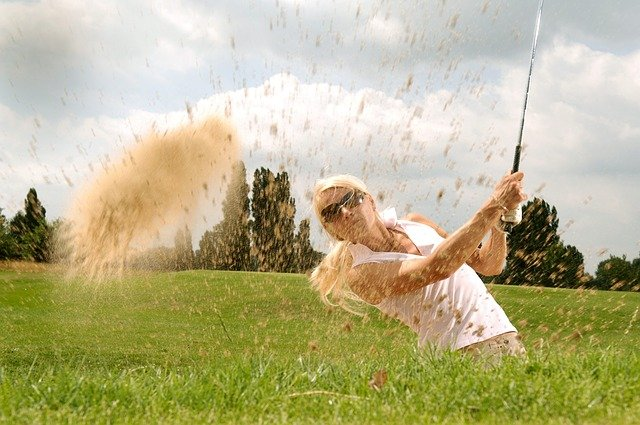 a woman golfing and hitting a ball