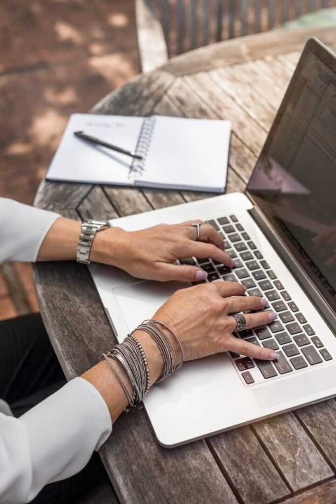 shot of woman's hands while she works on computer outdoors