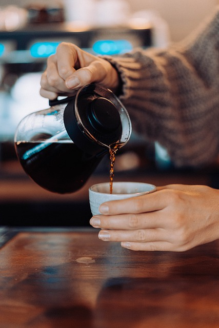 person pouring coffee into coffee cup