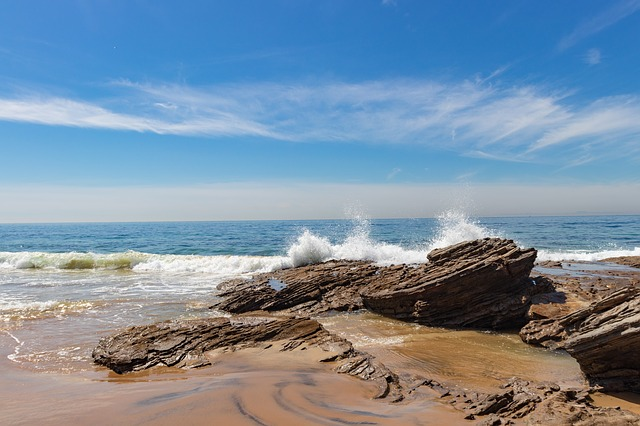 waves crashing over a rock at Crystal Cove State Park