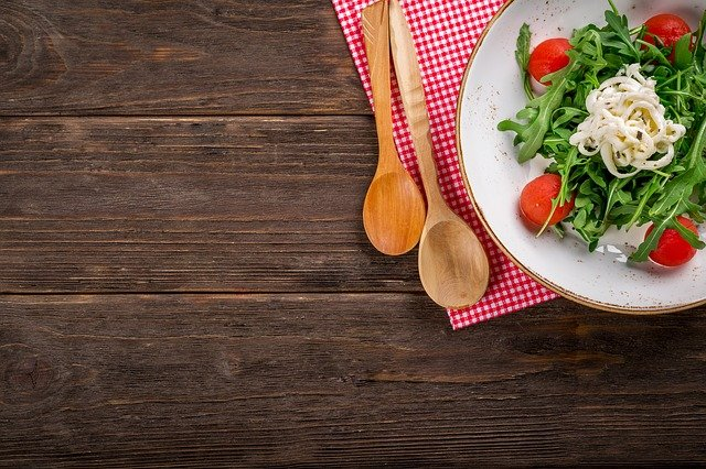 serving spoons on a wood table next to a plate of salad