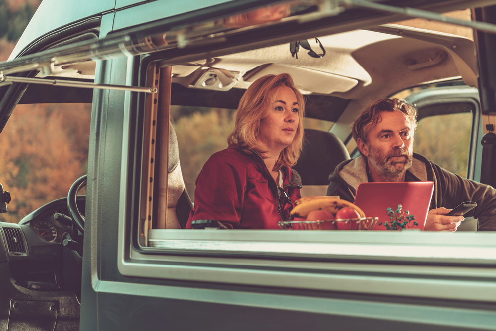 Couple Watching Exciting TV Game Inside Self Made Camper Van RV During Scenic Autumn Weekend Getaway.