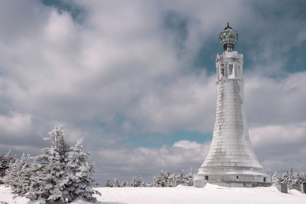 The top of Mount Greylock with Veterans Memorial at the summit in the winter next to the snowy trees.