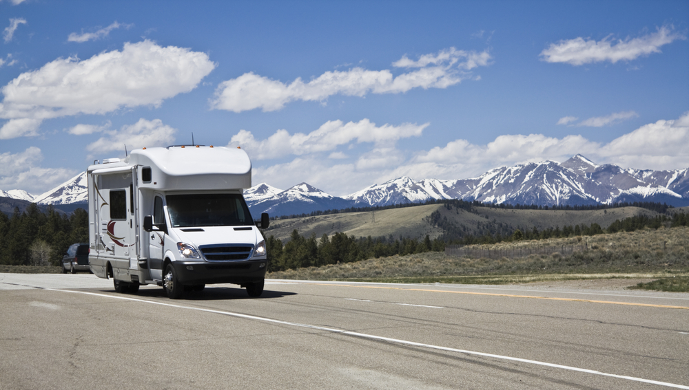 RV traveling on a three-lane highway with mountains, rolling hills, and blue sky with puffy, white clouds in the background