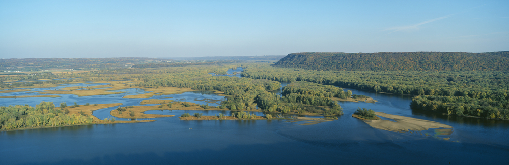 A river with several grassy, forested islands in Pikes Peak State Park, Iowa.