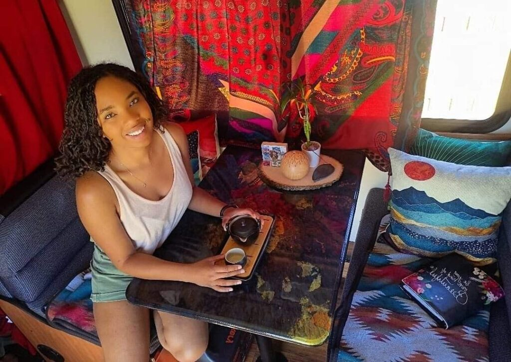 Woman smiles and sits at the table in her RV