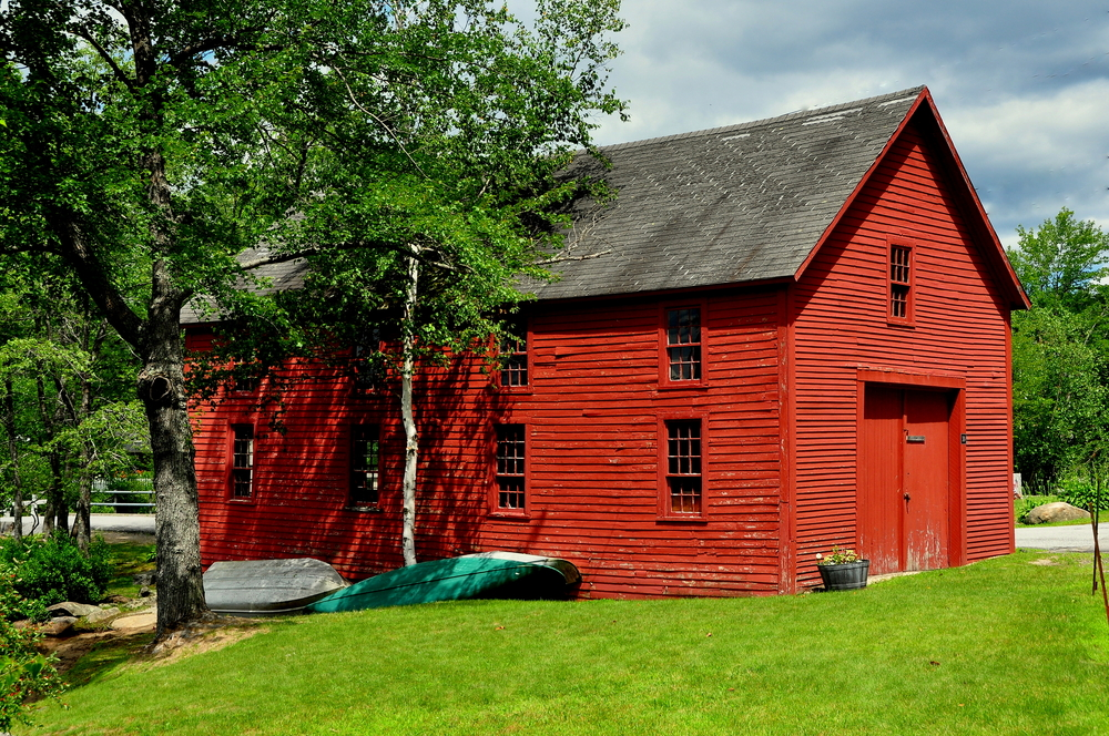 HARRISVILLE, NEW HAMPSHIRE: Two wooden rowboats lie next to a bright red barn in the village's historic district