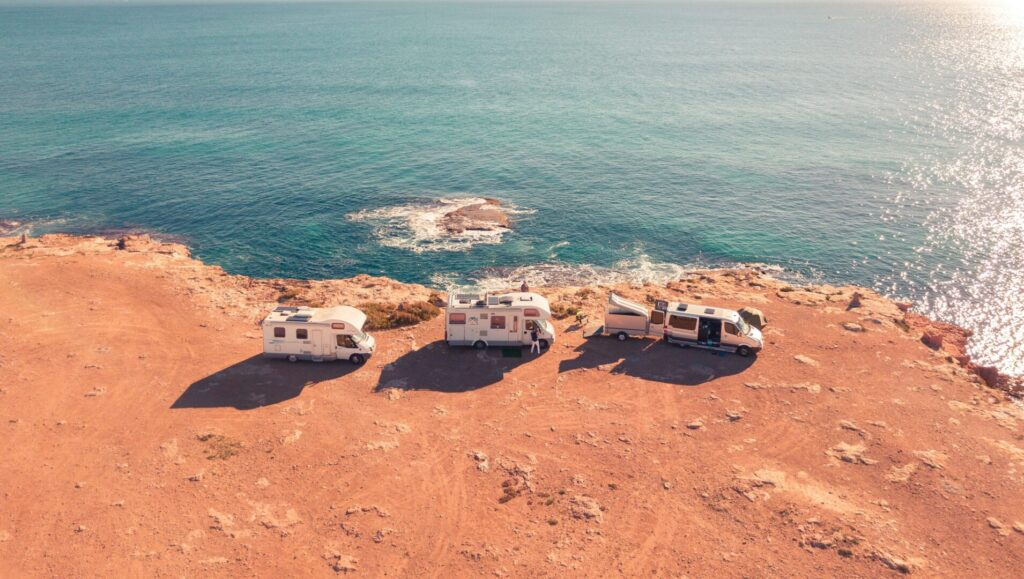 Three Class C RVs parked in a line along the coastline
