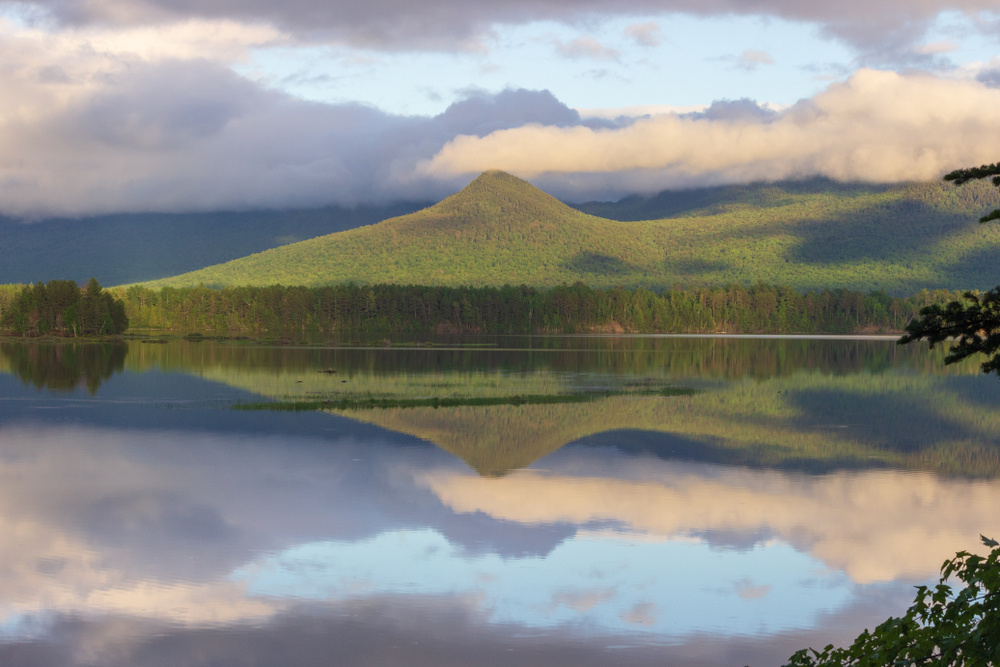 Floating clouds above a green forested mountain peak are reflected on the surface water of Flagstaff Lake in Maine