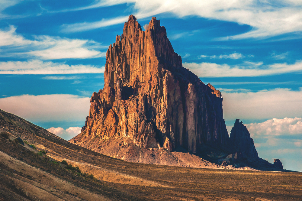A tall, jagged red-rock butte stands alone in an empty desert under a blue sky.