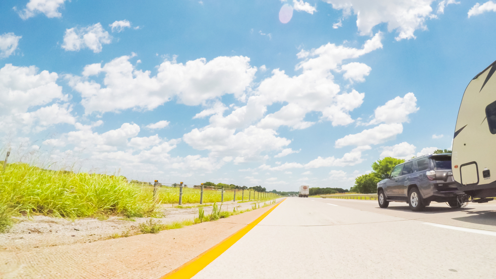 Car and RV trailer driving east in Kentucky under blue skies with patches of white cloud over an unlimited horizon