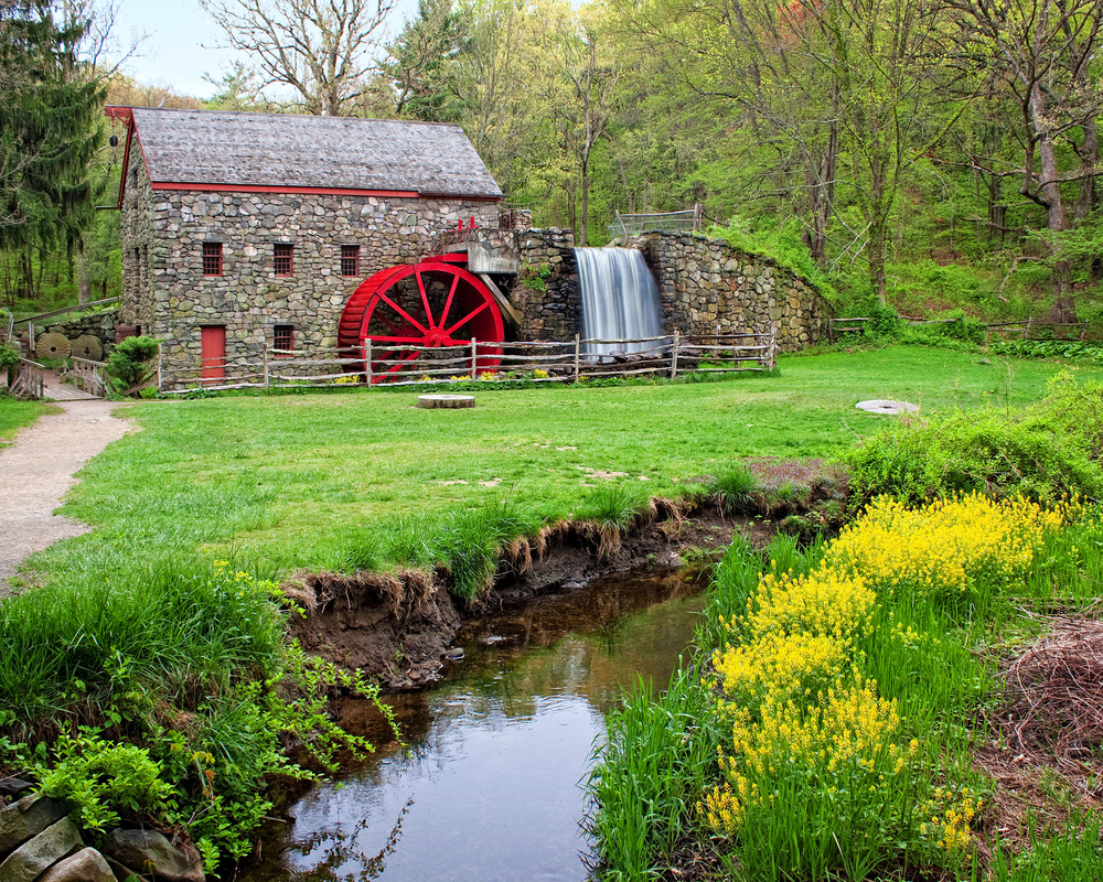 Historic grist mill with stone walls and bright red wheel sitting in a green meadow surrounded by green trees