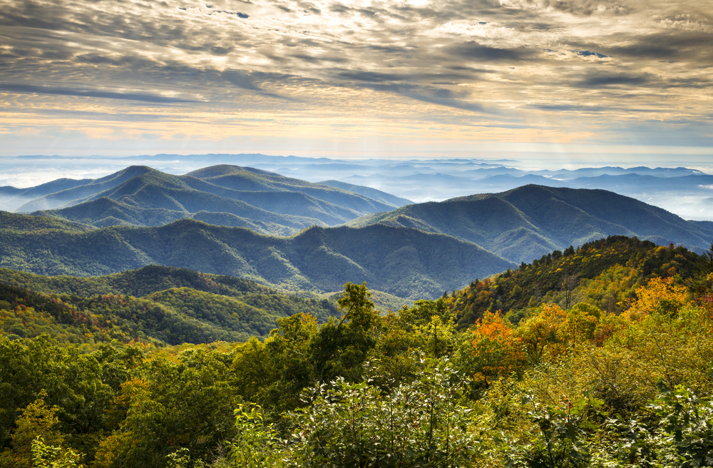A sweeping mountain range under a cloudy sky with sunlight peeking through and lush fall trees in the foreground.