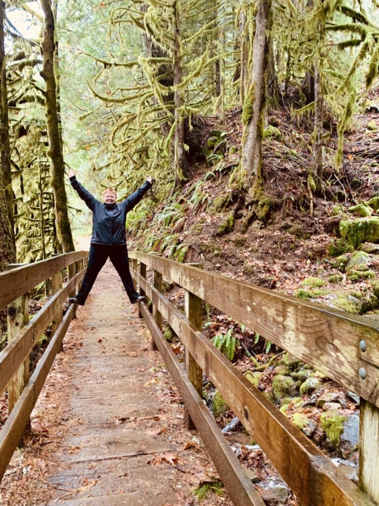 Woman balances on bridge in a forest