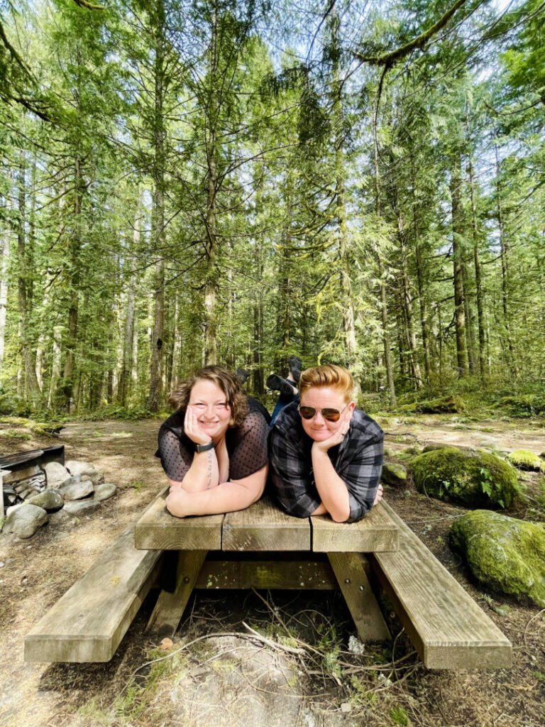 Women pose on a picnic table and smile