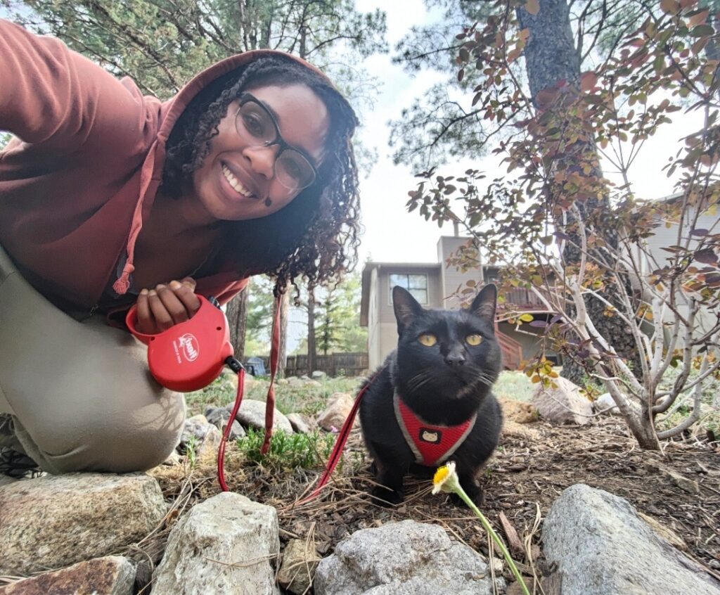 Young woman and her cat, who is wearing a leash and harness