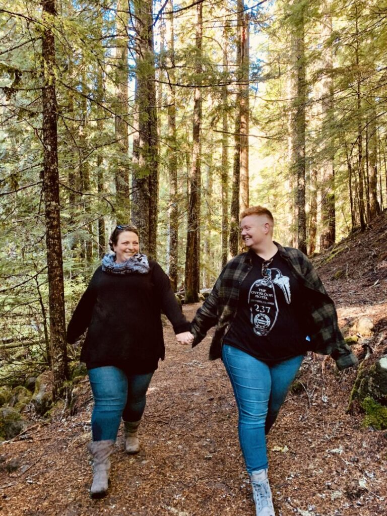Women hold hands and walk in forest