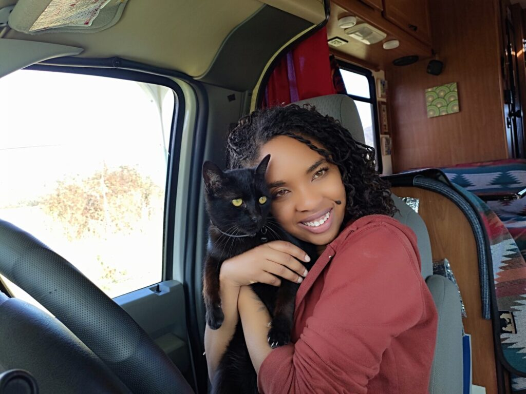 Young woman holds her cat seated at the wheel of her class c rv