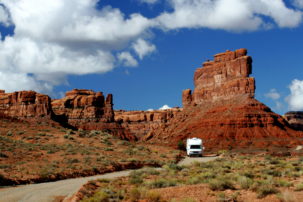 A white RV drives on a road next to the tall, rocky monuments of Utah's Valley of the Gods