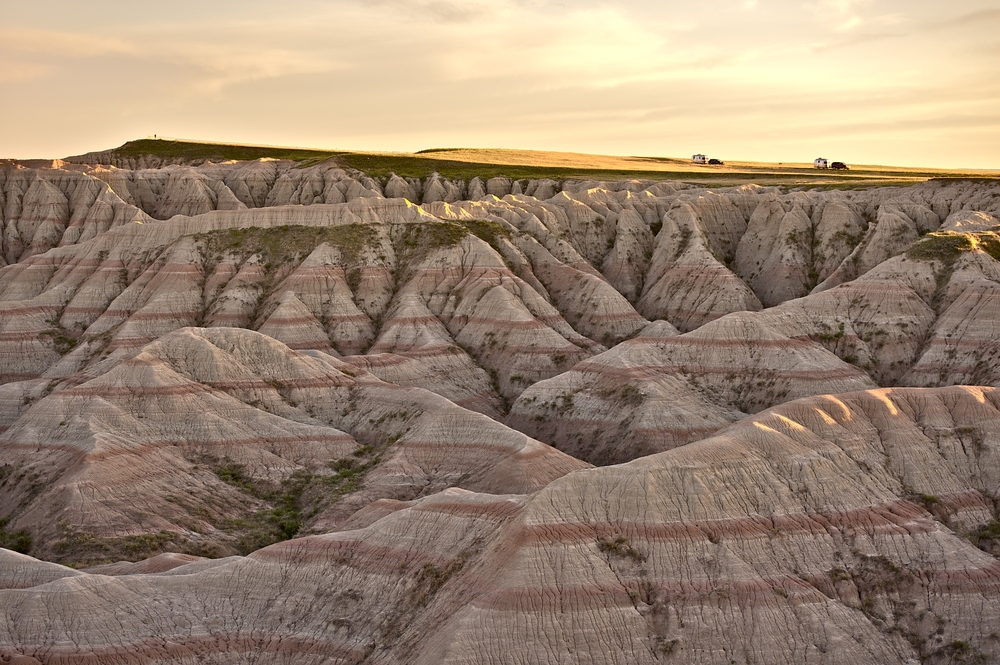 Heavily eroded pink rock formations descend from a plateau, on which two RV's are parked under a yellow, sunset sky.