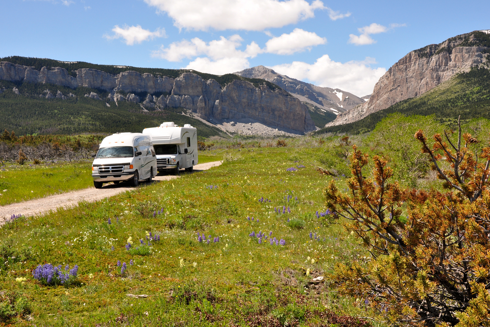 A camper van and an RV on a dirt road that runs from a grassy meadow to tall, rocky buttes