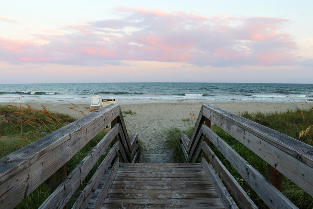 A wooden boardwalk with railings leads to an open, empty beach. The sun is still pink from the sunrise.