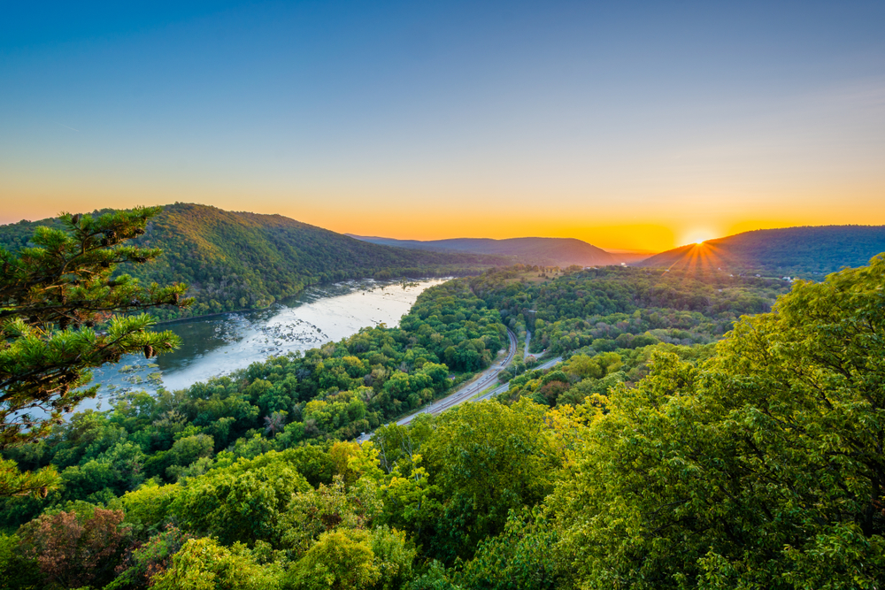 The sun rising over a valley, where a road travels parallel to a river.