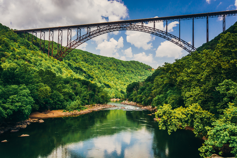 A long arched bridge spans high above a calm river with green trees on both sides.