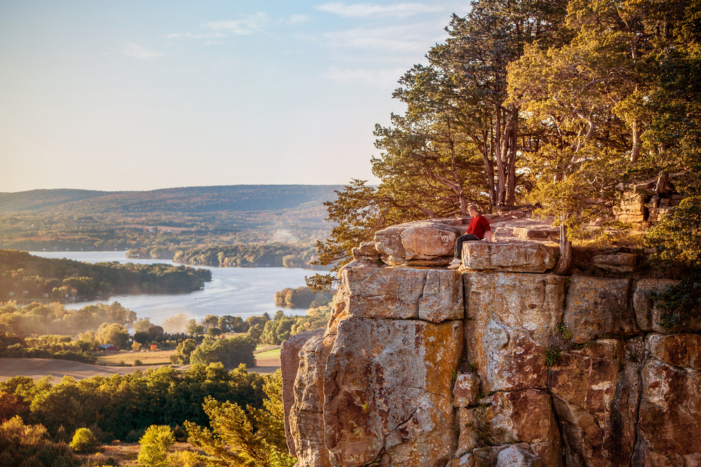A person sits on a rocky outcropping, high above fields of trees and a lake.