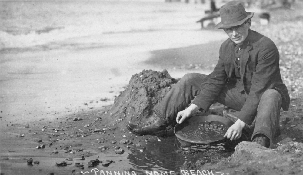 Man panning gold on Nome, Alaska beach in the early 20th century.