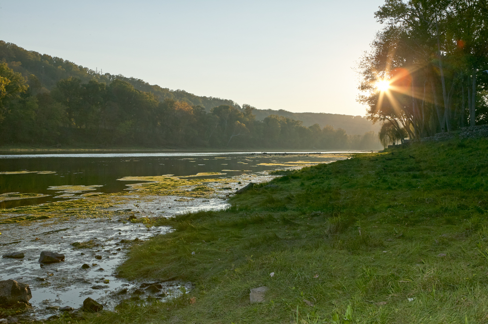 Star burst sun over the White River, Arkansas with early morning mist in a tranquil scenic landscape