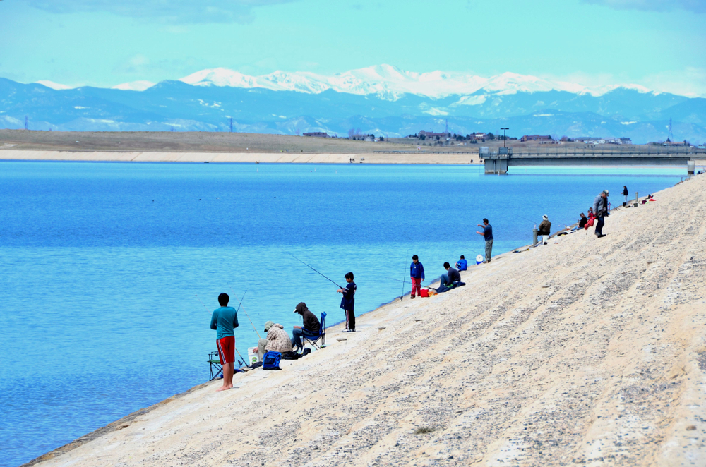 Aurora, Co, USA. March 9, 2007. Unidentified people fishing at the Aurora Reservoir in Aurora Colorado on a warm weekend with the Rocky Mountains in the background.