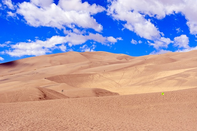 Great Sand Dunes National Park with a blue sky and puffy white clouds