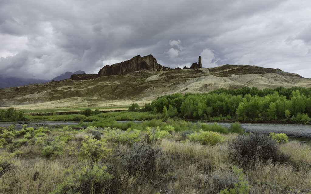 Cody, Wyoming, USA - Buffalo Bill State Park with a glimpse of the Shoshone River flanked by imposing mountain cliffs and bush land and cacti near Cody, Wyoming, USA.