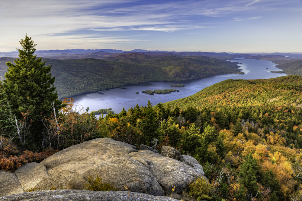 A rocky overlook on a mountain looks out towards a green and yellow forest and shining blue lake.