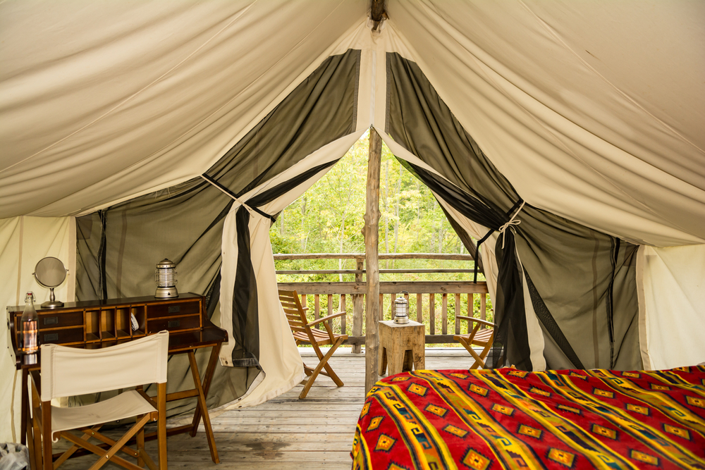 The inside of an elaborate tent with a bright blanket and unique desk under a canopy.