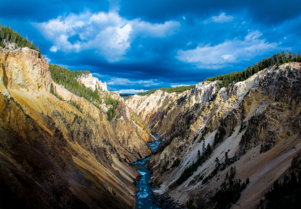 A river flows through the middle of a canyon with steep walls, under a blue, cloudy sky.