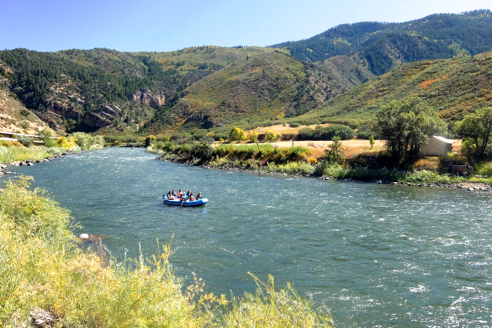 A group of people on a raft in a wide river, a cabin a little ways back from the shore.