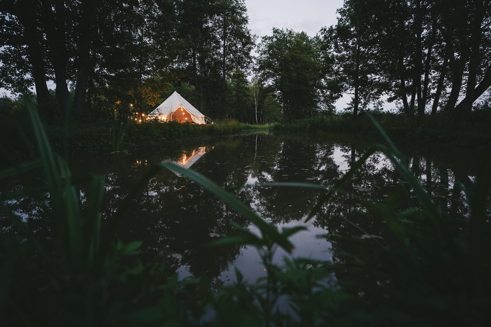 A small white tent with string lights sits along a river surrounded by trees